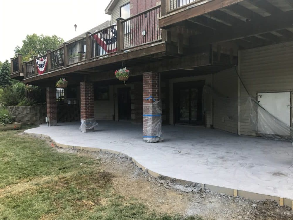 stamped and colored concrete patio under deck water drainage concrete retaining wall siding roofing omaha contractor - Patio Under Deck